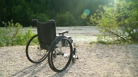 Slowmotion av den tomma rullstolen utanför i solig sommar parkera med ljust solsken på bakgrundsgräsplannaturen som lyfter solen stock video