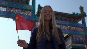 Slowmotion av en bloger för ung kvinna som rymmer ett litet kinesiskt flaggaanseende på den Quinmen Main Street gallerian Förbjud stock video