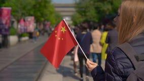 Slowmotion av en bloger för ung kvinna som rymmer en liten kinesisk flagga, gå den Quinmen Main Street gallerian Forbiddenet City stock video