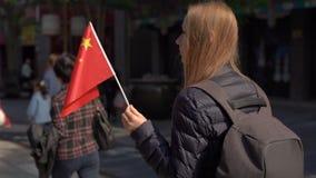 Slowmotion av en bloger för ung kvinna som rymmer en liten kinesisk flagga, gå den Quinmen Main Street gallerian Forbiddenet City arkivfilmer