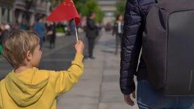 Slowmotion av pojken som rymmer en liten kinesisk flagga, gå lite den Quinmen Main Street gallerian Forbiddenet City i stock video