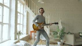 Slowmotion av rolig skäggig mandans på säng som hemma sjunger och spelar den elektriska gitarren i sovrum stock video