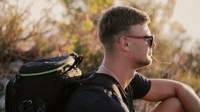 Slowmotion av stiligt barn dana bärande solglasögon för mannen, och ryggsäcken ser solnedgång i fältet closeup 1920x1080 stock video