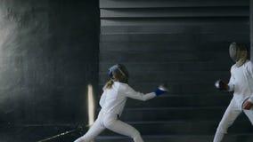 Slowmotion av två fäktare mannen och kvinnan ha fäktningen som inomhus utbildar lager videofilmer