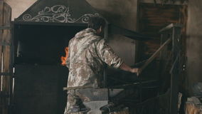 Slowmotion of Bearded man blacksmith burning original forge fireplace with air at historical smithy indoors stock video