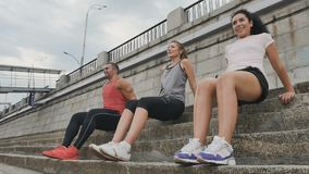 Sporty people do push-ups. Slowmotion. The camera shoots from below. Young sporty brunette man, handsome brunette and blonde women sit at the stairs. Attractive stock video