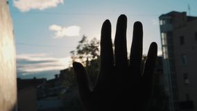 Slowmotion close up silhouette of palm hand blocking bright sun light outside. Buildings and trees on background stock footage