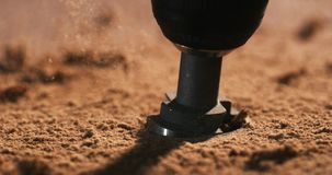 Slowmotion closeup of a drill boring through wood. Sending up clouds of sawdust stock video