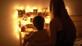 Slowmotion closeup shot of a mother and her little son look at an advent calendar hanging on a bed lighten with. Christmas lights. Getting ready for Christmas stock video