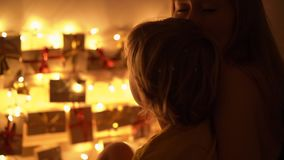 Slowmotion closeup shot of a mother and her little son look at an advent calendar hanging on a bed lighten with. Christmas lights. Getting ready for Christmas stock video footage