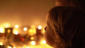 Slowmotion closeup shot of a mother and her little son look at an advent calendar hanging on a bed lighten with. Christmas lights. Getting ready for Christmas stock footage