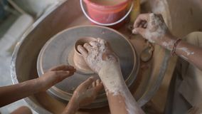 Slowmotion closeup shot of a teacher potter teaching his apprentice how to make a clay bowl on a Potter`s wheel