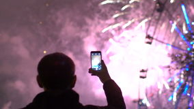 Slowmotion of closeup silhouette of man watching and photographing fireworks explode on smartphone camera outdoors stock video footage