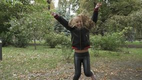Cute little girl rejoices in the park in slowmotion stock video