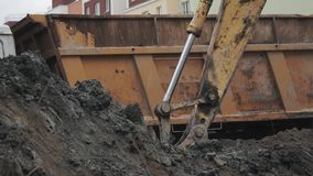 Slowmotion excavator bucket dig soil and dump in back of truck at building site stock video