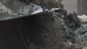 Slowmotion excavator bucket pulling concrete plate under pile of soil and dirt stock footage
