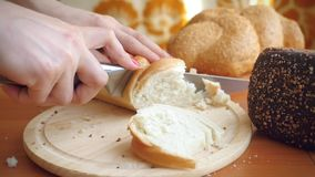Slowmotion of Female hands cut French bread knife stock video footage