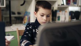 Slowmotion footage of a little boy with big blue eyes portrait, sitting in front of the laptop screen. Programming class. Educational process stock video footage