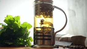 Slowmotion of glass teapot with blooming tea stock footage