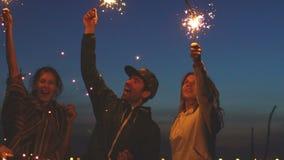 Slowmotion grupa młodzi przyjaciele ma wyrzucać na brzeg przyjęcia Przyjaciele tanczy i świętuje z sparklers w zmierzchu zbiory wideo