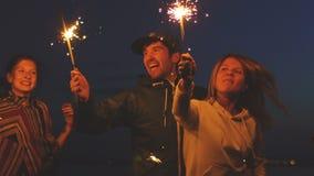 Slowmotion grupa młodzi przyjaciele ma wyrzucać na brzeg przyjęcia Przyjaciele tanczy i świętuje z sparklers w zmierzchu zdjęcie wideo