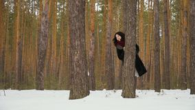 Pretty woman and little girl peers out of the tree in winter forest. Slowmotion. Handsome woman peers out of the tree in the winter forest with her little stock footage