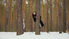 Young woman with her daughter peers out of the tree in winter forest. Slowmotion. Handsome woman peers out of the tree in the winter forest with her little stock footage