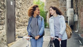 Slowmotion of happy attractive young women tourists laughing and walking with bikes along street with beautiful old stock video