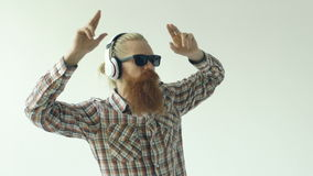 Slowmotion of Happy young bearded man in sunglasses and headphones dancing and listen music on white background stock video footage