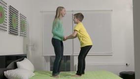 Slowmotion - Kleine jonge geitjes die op bed in slaapkamer springen stock videobeelden