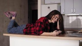 Slowmotion längd i fot räknat av en ung flicka som ler och skrattar whilelying på hennes köksbordyttersida och att smsa någon arkivfilmer