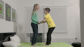 Slowmotion - Little kids jumping on bed in bedroom. Slow motion - Little kids jumping on bed in bedroom stock video footage