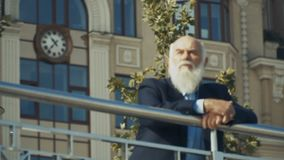 Handsome senior man enjoys urban view from observation deck. Slowmotion. Old gray-haired man wearing suit is outdoors. Intelligent elderly man stands near the stock footage