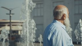 Gray-haired man walks near the fountain. Slowmotion. Old man wearing suit walks over the city. Man slowly walks under the splashes. Male walks under the splashes stock video