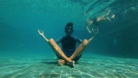 Slowmotion onderwaterschot van een jonge mens in een yoga stelt het mediteren op de bodem van een zwembad Hij is langs gestoord stock video