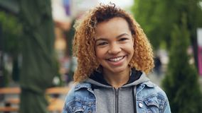 Slowmotion portrait of attractive African American girl looking at camera, smiling, laughing and touching her hair stock video
