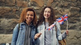 Slowmotion portrait of two female friends foreign students in the UK waving British flags and laughing looking at camera. Slowmotion portrait of two female stock video footage