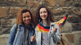 Slowmotion portrait of two smiling girls friends waving German flags and looking at camera standing against stone wall. Slowmotion portrait of two attractive stock video footage