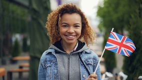 Slowmotion portrait of young and pretty African American lady holding British flag and smiling looking at camera on stock footage