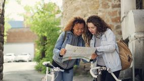 Slowmotion of pretty girls tourists looking at map and talking standing in street in foreign city with bicycles. Bike stock footage