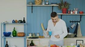 Slowmotion Przystojny młody śmieszny mężczyzna taniec, śpiew w kuchni i podczas gdy surfujący ogólnospołecznych środki na jego sm zbiory