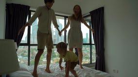 Slowmotion schot van een familie die op een bed springen Matras en hoofdkussenconcept stock video