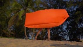 Slowmotion schot van een jonge mens blaast een opblaasbare bank op een mooi strand op stock videobeelden