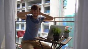 Slowmotion schot van een jonge mensenzitting op een balkon met een notitieboekje en het lijden aan een hevig lawaai dat door a wo stock video