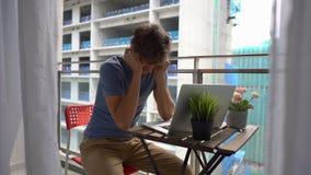 Slowmotion schot van een jonge mensenzitting op een balkon met een notitieboekje en het lijden aan een hevig lawaai dat door a wo stock footage