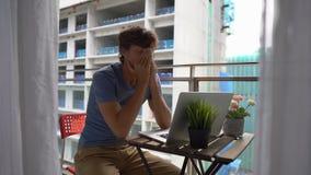 Slowmotion schot van een jonge mensenzitting op een balkon met een notitieboekje en het lijden aan een hevig lawaai dat door a wo stock videobeelden