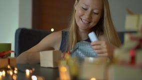 Slowmotion schot van een jonge vrouw pakt voorstelt in Heden in ambachtdocument wordt verpakt met een rood en gouden lint dat voo stock video