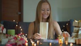Slowmotion schot van een jonge vrouw pakt voorstelt in Heden in ambachtdocument wordt verpakt met een rood en gouden lint dat voo stock videobeelden