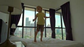 Slowmotion schot van een kleine jongen die op een bed springen Matras en hoofdkussenconcept stock videobeelden