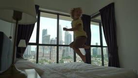 Slowmotion schot van een kleine jongen die op een bed springen Matras en hoofdkussenconcept stock footage
